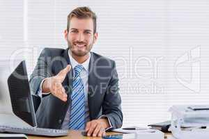 Businessman offering a handshake at office desk