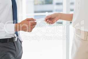 Mid section of executives exchanging business card