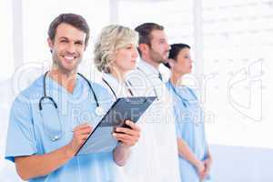 Male doctor writing reports with colleagues in medical office