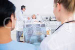 Rear view of doctors with blurred patient in hospital