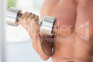 Mid section of a sporty young man with dumbbell
