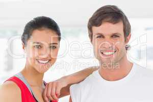 Closeup of a fit smiling couple in exercise room