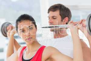 Male trainer helping fit woman to lift the barbell