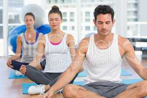 People in meditation pose with eyes closed at fitness studio