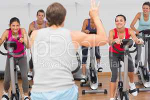 Trainer and fitness class at spinning class