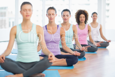 Sporty women in meditation pose with eyes closed at fitness stud