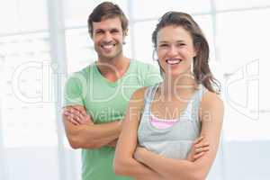 Fit young couple with arms crossed in exercise room