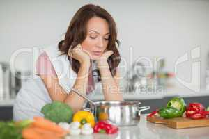 Serious woman preparing food in kitchen