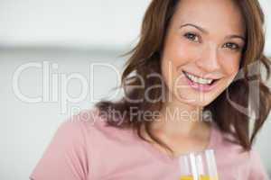 Closeup of a smiling woman holding orange juice