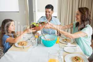 Happy family of three sitting at dining table