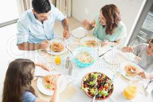 Family of four sitting at dining table