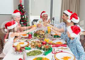 Family in santas hats toasting wine glasses at dining table