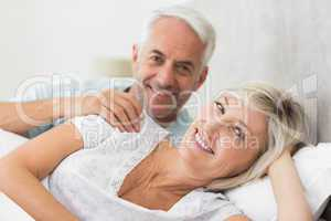 Closeup of a smiling mature couple lying in bed