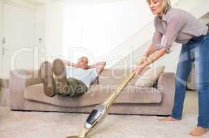 Man resting on couch while woman vacuuming area rug