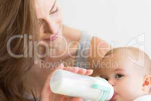 Closeup of mother feeding baby with milk bottle