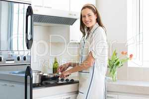 Smiling young woman preparing food in kitchen