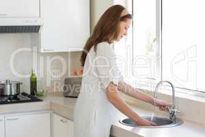 Woman washing glass at washbasin in kitchen