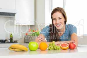 Smiling woman with fruits on kitchen counter