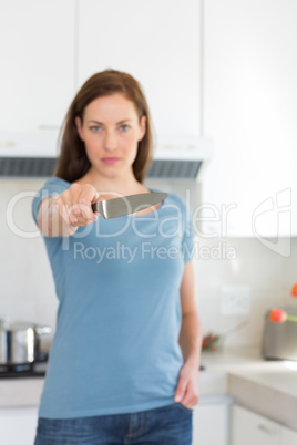 Serious woman holding out knife in kitchen