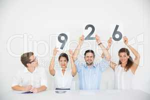 Business people holding score signs