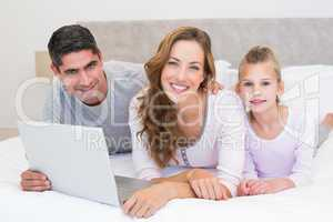 Family with laptop in bed