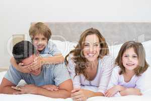 Happy family lying together in bed