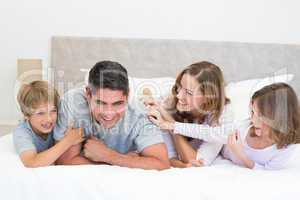 Playful family in bed