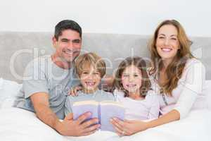 Happy family with storybook in bed