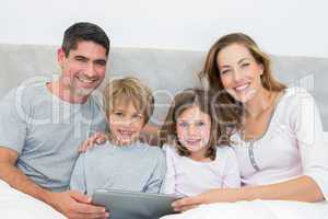 Family with digital tablet in bed