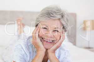 Senior woman with head in hands on bed