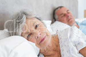 Senior woman lying with man in background