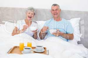 Happy senior couple having breakfast in bed