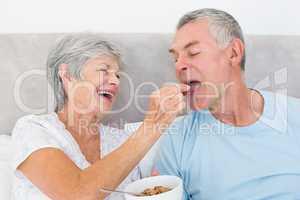 Loving senior woman feeding cereals to husband
