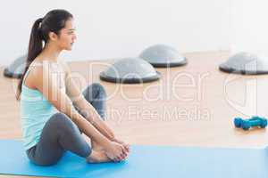 Fit woman doing butterfly stretch in exercise room