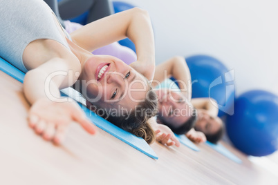 Fit class exercising in row at fitness studio