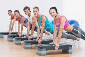 Fitness class doing step aerobics exercise