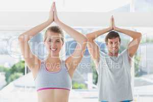 Sporty couple with joined hands in fitness studio