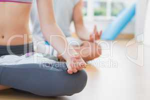 Sporty couple in meditation pose at fitness studio