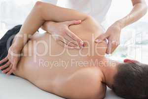 Physiotherapist massaging man