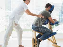 Female therapist massaging man in hospital