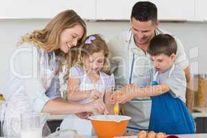 Family mixing egg to bake cookies