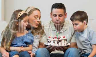 Family blowing candles on cake