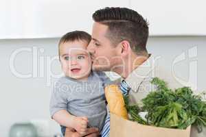 Loving businessman kissing baby boy