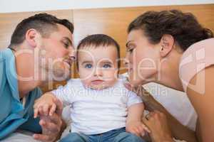 Parents kissing baby on cheek