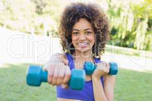 Woman lifting free weights in park