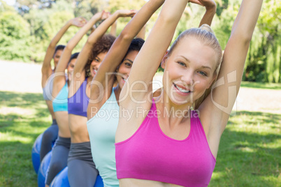 Row of sporty women stretching