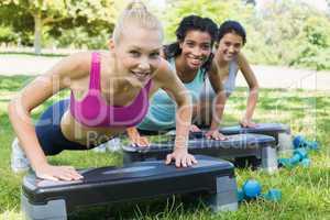 Sporty women doing step aerobics