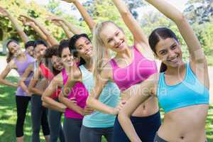 Multiethnic friends doing stretching exercise at park