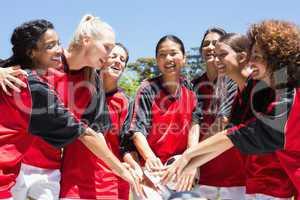 Female soccer team stacking hands