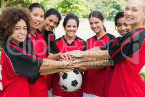 Confident soccer team stacking hands on ball